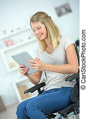 Young disabled woman using a tablet computer