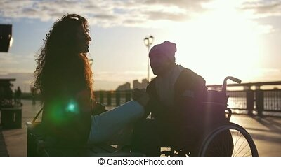 Young disabled young man in a wheelchair with young woman enjoying the sunset together