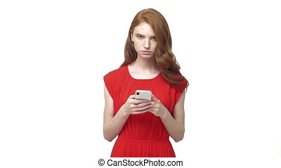 Young displeased annoyed woman with long red hair typing...