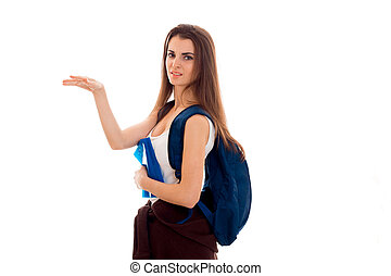 young displeased brunette student girl with backpack on her shoulders and books in her hands pointing to the side and looks at the camera isolated on white background