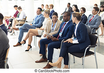 Young diverse executives sat in conference room, speaking