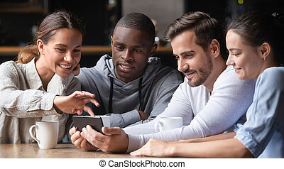 Young diverse friends looking at smartphone using apps in cafe