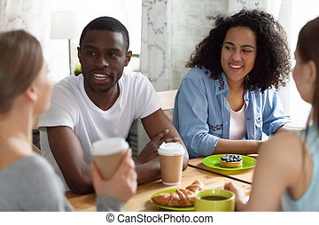 Young diverse friends sitting at table in cafe