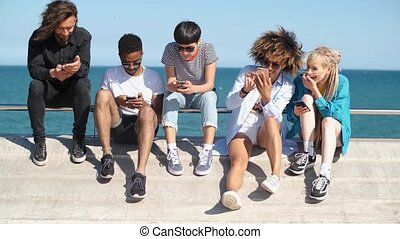 Young diverse people with mobile phones on seafront - Cool...