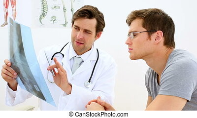 Young doctor discussing xray with his patient in his office...