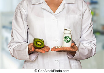 Young doctor holding kiwi and bottle of pills with vitamin C and