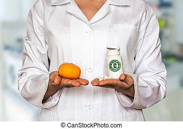 Young doctor holding mandarin and bottle of pills with vitamin C