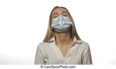 Young doctor in a medical mask is experiencing a migraine at work, massaging the temporal lobes of the head, looking at the camera. Isolated on white background. High quality 4k resolution footage.