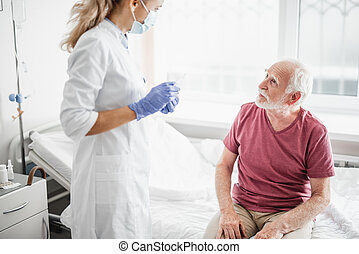 Young doctor in protective mask talking with patient
