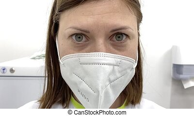 Young doctor in the mask. Closeup portrait of female doctor in clinic.