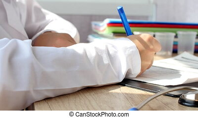Young doctor is writting a prescription. Female doctor doing...