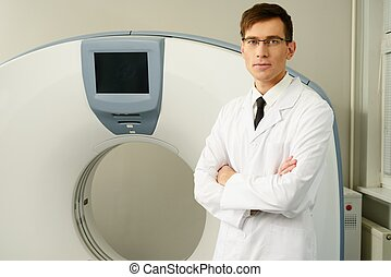 Young doctor standing near computed tomography scanner in a hospital