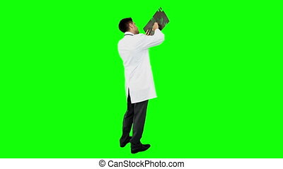 Young doctor standing with x-ray on green screen background