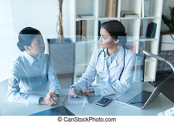 young doctor talking with patient during medical consultation at office