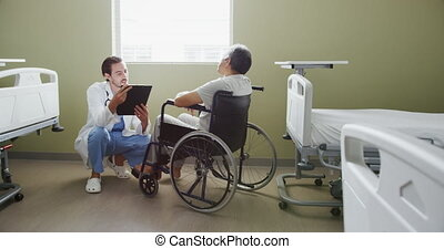 Young doctor talking with patient in a wheelchair 4k