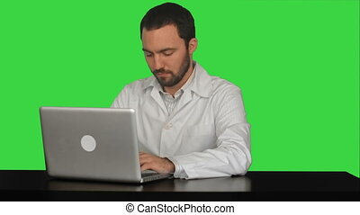 Young doctor thinking idea with laptop computer on the table on a Green Screen, Chroma Key