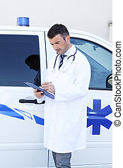young doctor writing in front of ambulance