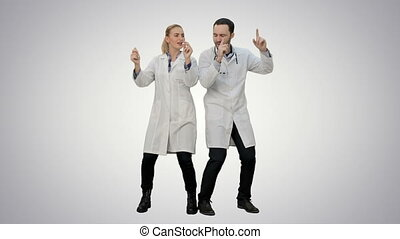 Young doctors in a good mood dancing and singing songs on white background.
