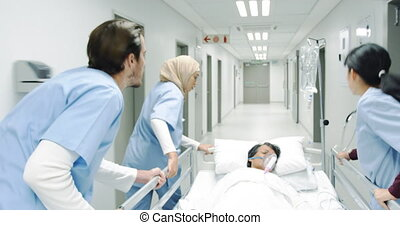 Young doctors pulling hospital bed rushing 4k - Follow shot ...