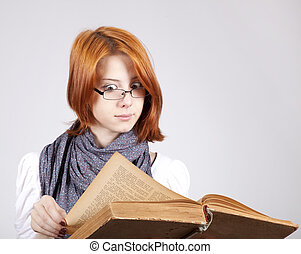 Young doubting fashion girl in glasses with old book