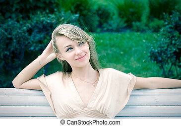Young dreamy woman resting in a park