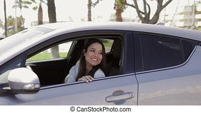 Young driver waving hand to friend - Young excited girl...