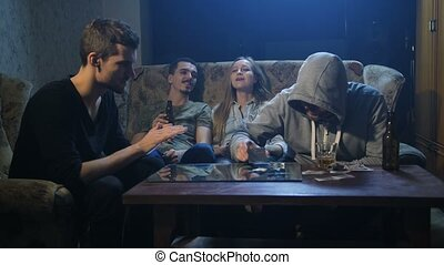 Young drug addicts sitting on the couch indoors - Four young...