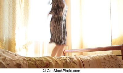 young drunk arab girl funny jumping on a bed.
