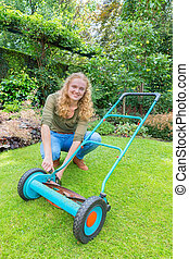 Young dutch woman reparing lawn mower in garden