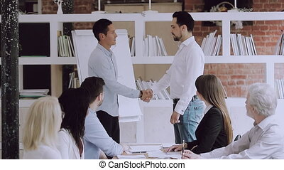 Young eastern ethnicity boss shaking hands with smiling intern. Different ages diverse employees watching confident leader praising happy colleague or thanking for help at brainstorming meeting.