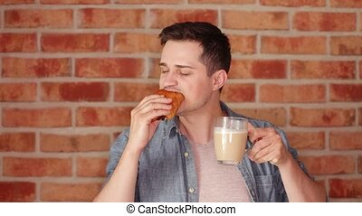Young eating a bun and drinking a coffee on blick wall...