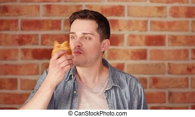 Young eating a croissant on blick wall background