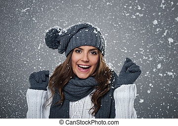 Young ecstatic woman enjoys first snow