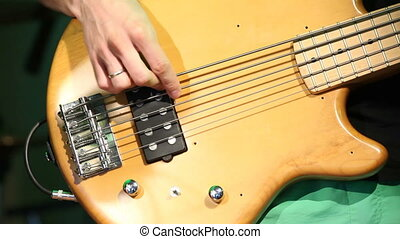 Young electric guitarist player playing bass guitar, closeup