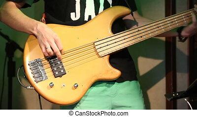 Young electric guitarist player playing bass guitar, closeup