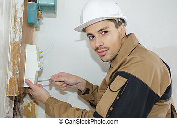 young electrician builder engineer installing a fuse box