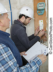 young electrician builder engineer screwing equipment in fuse box