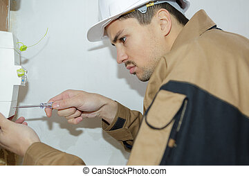 young electrician engineer worker in front of fuse switch board