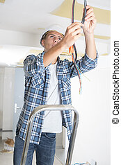 young electrician fixing cables on the ceiling
