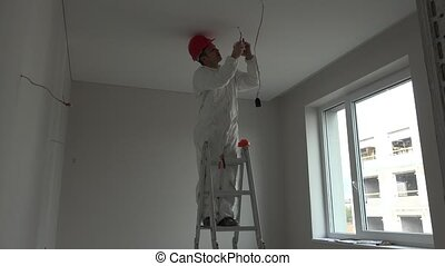 Young electrician installing smoke detector fire alarm on ceiling