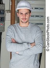 young electrician posing arms crossed at workplace