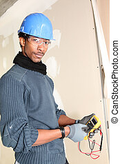 Young electrician with multimeter