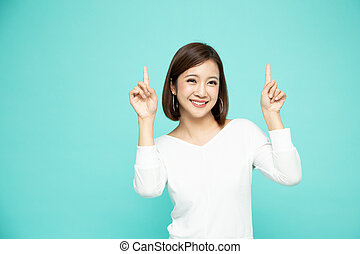 Young elegant beautiful Asian woman smiling and pointing to empty copy space isolated on green background