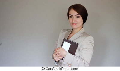 Young Elegant beautiful woman smiling, winks and looking at the camera. Businesswoman, Secretary or assistant manager.