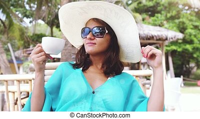 Young elegant brunette woman wearing hat and sunglasses on holiday, sitting in beach cafe with scenic views of the sea and palm trees drinks tea has a breakfast. slow motion. 3840x2160