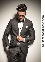 Young elegant business man looking down while holding his...