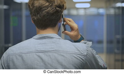 Young, elegant businessman goes in his office and talk on a mobile phone