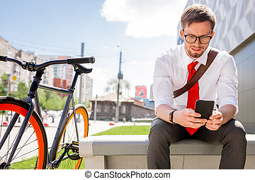 Young elegant businessman watching online video or reading message in smartphone