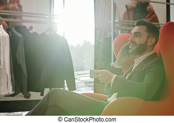 Young elegant businessman with cup of tea talking to client by mobile phone