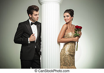 young elegant couple looking at each other near column